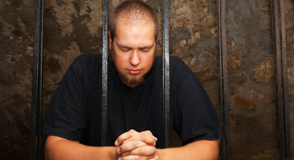 man praying in prison